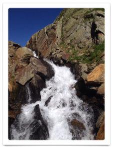 Rheinquelle sprudelt in einer wilden Kaskade durch Felsen, weißes Wasser, blauer Himmel.