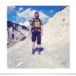 Wanderer mit Rucksack (Irgendlinck, also ich) posiert vor fast weißem Geröll und blauem Himmel. Das Bild ist quadratisch auf Postkarte, weiß