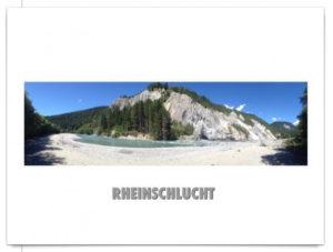 Panoramabild des Rheins, im Vordergrund Rheinstrand, im Hintergrund Felsen und Fichtenwald, blauer Himmel, Hintergrund der Postkarte ist weiß.