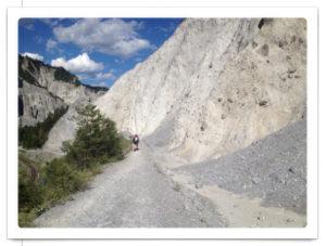 Graue, fast weiße Bergwanderszene, Weg fluchtet gegen blauen Himmel, winzig ein Wanderer mit Rucksack