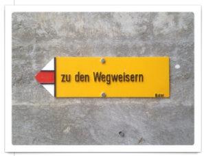 Ein gelbes Wanderwegschild, auf dem geschrieben steht 'zu den Wegweisern', zeigt nach links.