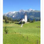 Landschaftsbild in den Bergen, Wiese, Kirche, im Hintergrund schneebedeckte Felsen.