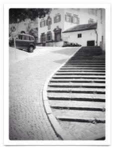 Straßenszene in Chur, Schwarz-weiß, die hälfte des Bildes zeigt eine geschwungene Treppe