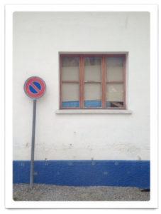 Parkverbotsschild neben einem Fenster, die Hauswand hat einen blauen Sockel.