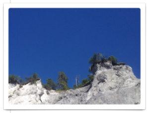 Brüchiger, grauer, fast weißer Fels in der Rheinschlucht vor blauem Himmel
