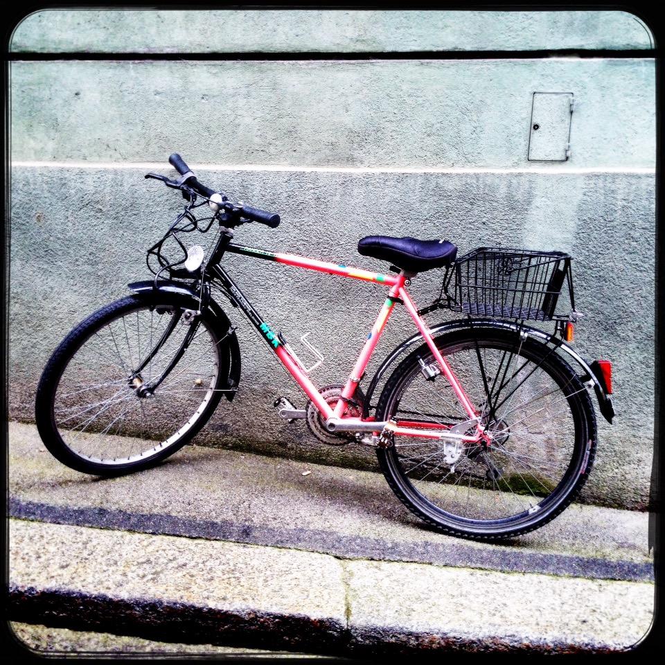 Rosa Fahrrad lehnt an einer grauen Wand. Quadratisches Retrobild.