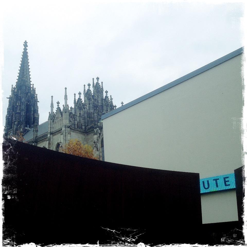 In einem Spalt sieht man rechts unten im Bild den Schriftzug UTE. Im Hintergrund über verschachtelten Wänden, links oben im Bild eine Kirche.