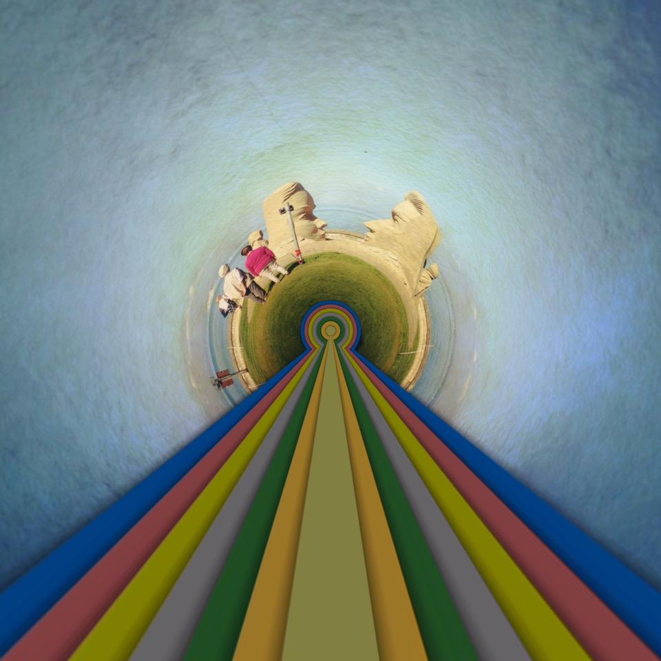 Eine blass regenbogenfarbene Spur fluchte in die Bildmitte. Dort wölben sich Sandskulpturen und ein par Menschen wie auf dem Rund eines winzigen Planeten. Die überlebensgroßen Skulpturen erinnern ein bisschen an die Osterinsel-Skulpturen.