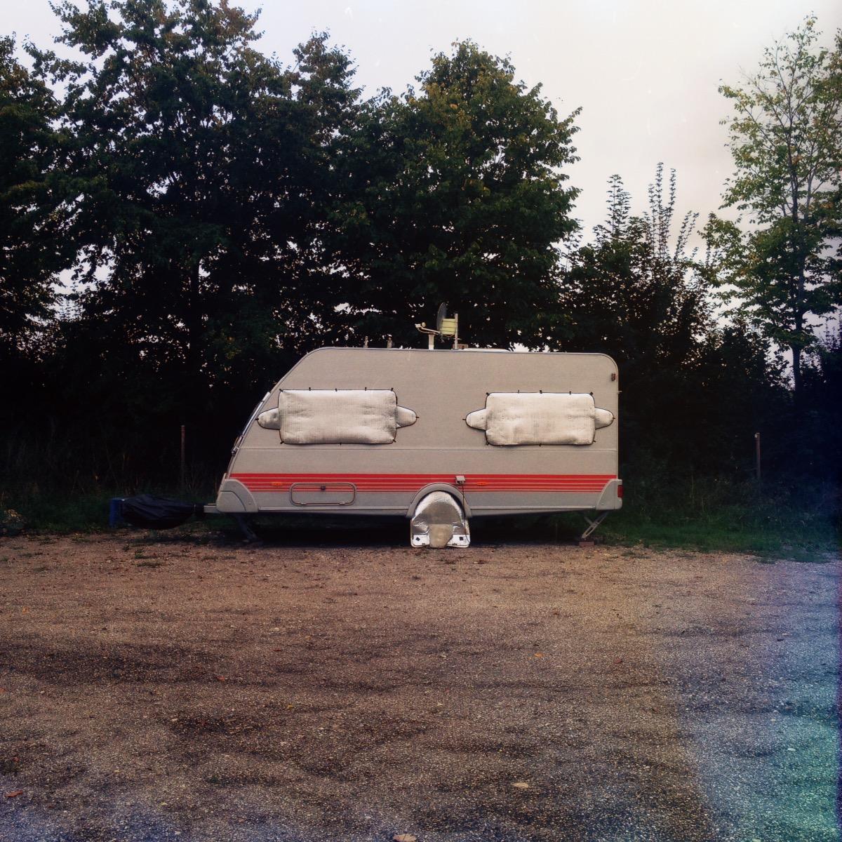 Ein Wohnwagen im Profil, der mit seinen verhangenen Fenstern anmutet wie ein Gesicht mit geschlossenen Augen.