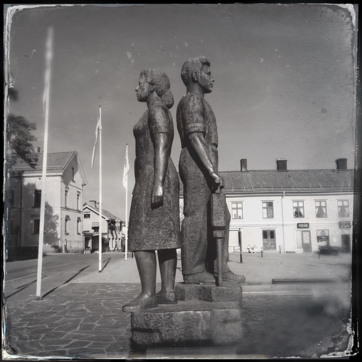 Sculpture of a boy and a girl standing back to back. On a marketplace. In the background wooden houses.